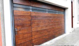 Portón basculante con puerta interna incluida, terminación en madera y ventanillas en la parte superior-
