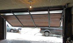 Portón basculante con puerta interna incluida, terminación en madera y ventanillas en la parte superior